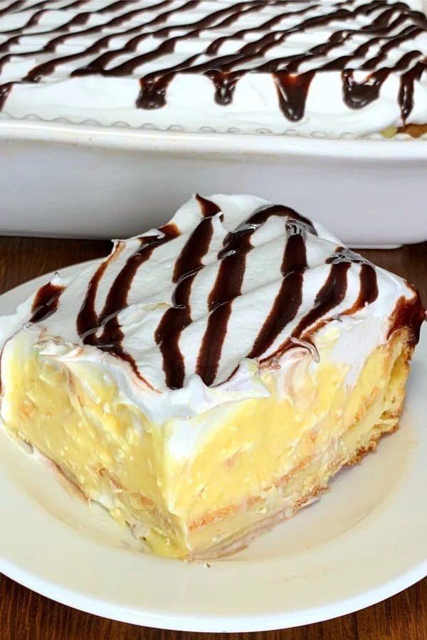 Piece of Cream Puff Dessert Cake with pastry puff layer, creamy pudding and cream cheese layer topped with whipped topping and chocolate syrup drizzle