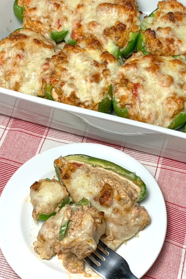 Oven baked Keto stuffed green peppers with lots of cream cheese in bakign dish and on a plate with a fork