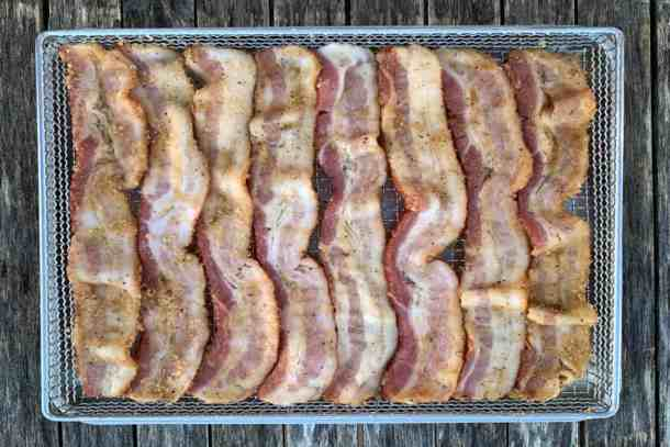 Raw bacon in air fryer tray or basket on wood background