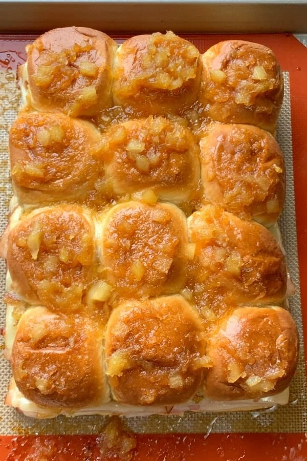 12 Hawaiian roll sliders with sweet pineapple glaze on baking sheet