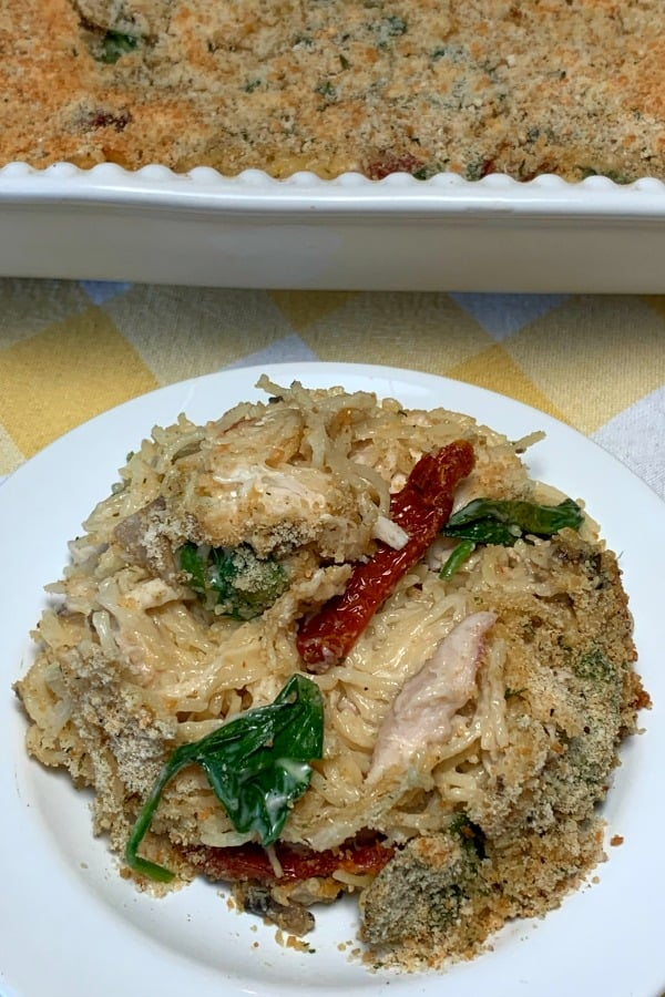 sundried tomatoes, spinach and alfredo sauce mixed in chicken and spaghetti on a white plate