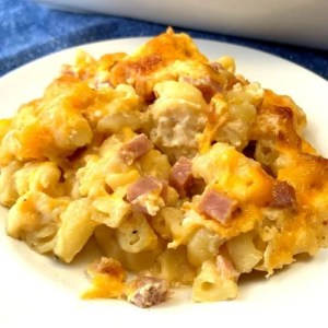 White plate of mac and cheese casserole with ham