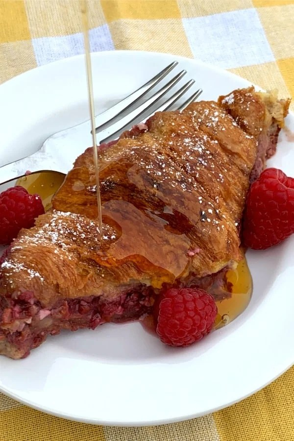 Croissant French toast with maple syrup and raspberry cream cheese filling on white plate on yellow plaid napkin