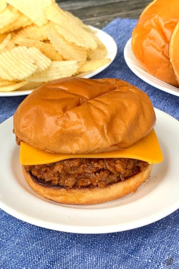 Crock pot sloppy Joe sandwich on white plate and blue napkin by chips to & buns