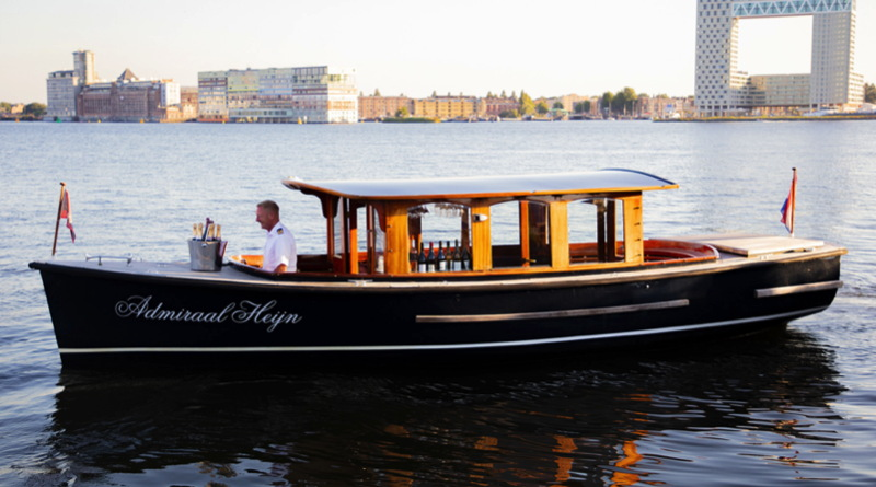 A classic 30 foot saloon boat with wooden fittings sits in a canal in Amsterdam