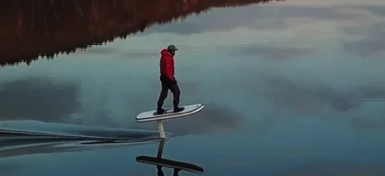 A man in a parka and snowpants is riding a flying surfboard in the winter