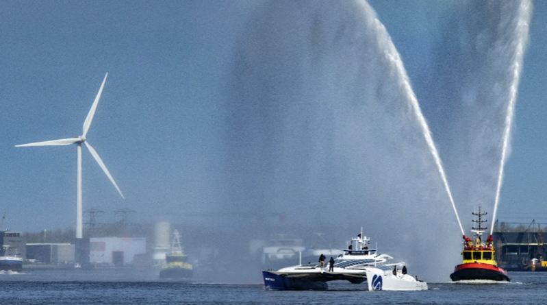 A futuristic catamaran sailing ship in Amsterdam harbour with fireboats spraying celebratory water