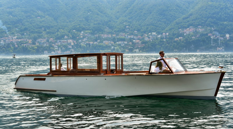 A classic wooden motorboat on Italy's Lake Como with mountains behind