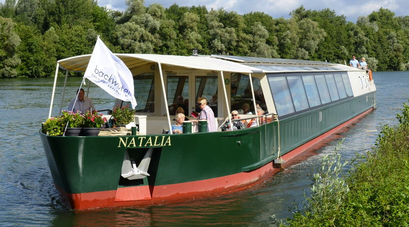 a long canal boat with observation windows cruises along a narrow waterway lined with trees