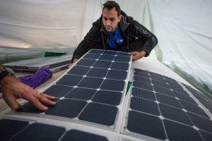 A man applies flexible solar panels to the deck of the Energy Observer