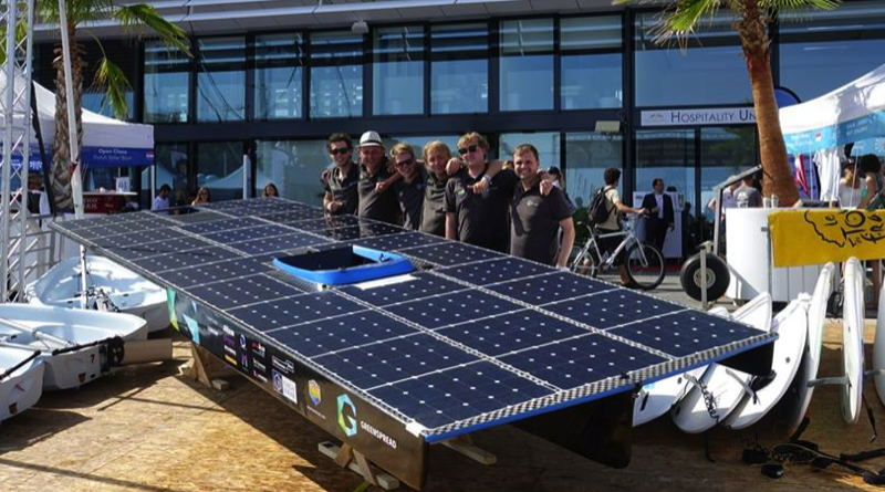 a university solar boat team poses with their boat