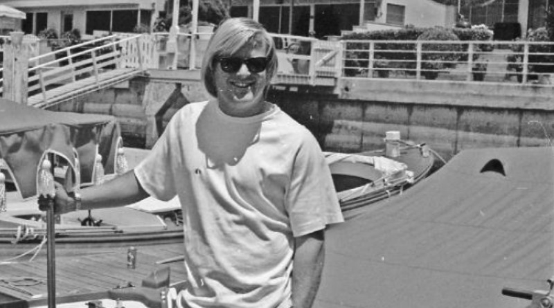 A blonde 'California beach bum' young man in 1972 stands in front of an electric boat