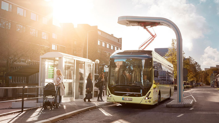 an electric bus on a city street being charged with an overhead system
