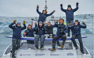 The crew of the Energy Observer renewable energy ship stand on the ship in the arctic celebrating and cheering