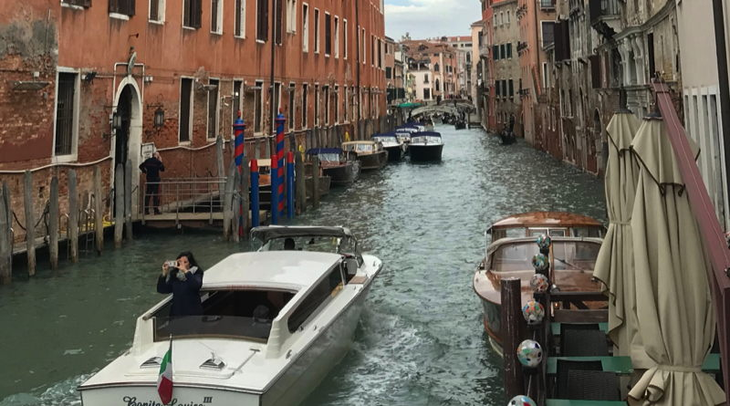 A bunch of motorboats are crowded into a Venice canal