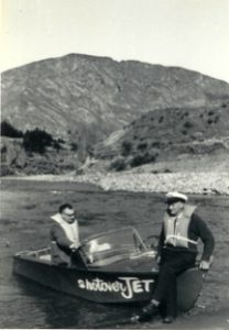 two men beside a small runabout boat in 1965