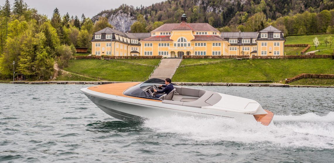 Marian M800 electric boat crusing along a lake in front of a chateau