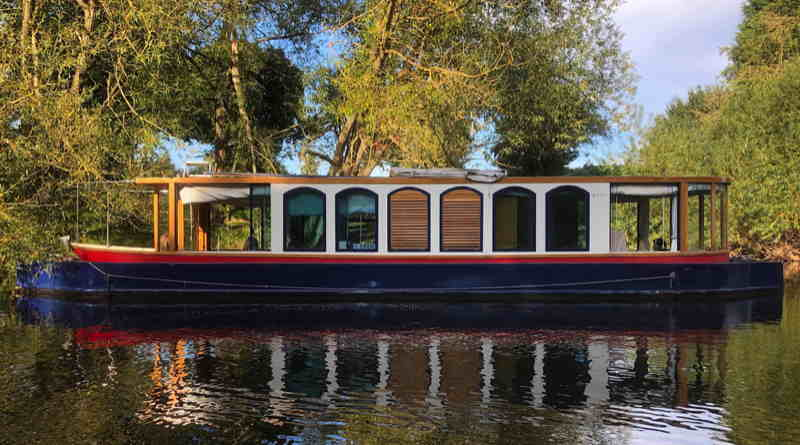 An electric narrowboat with arched windows on the River Thames