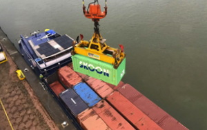 The Amsterdam floating battery being loaded onto a diesel electric barge along with cargo containers the same size