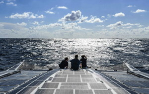 3 crew members of hydrogen ship sitting on solar panelled deck in middle of the Atlantic