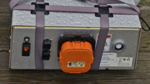 a demo electric boat battery pack held together with bungee cords and cables