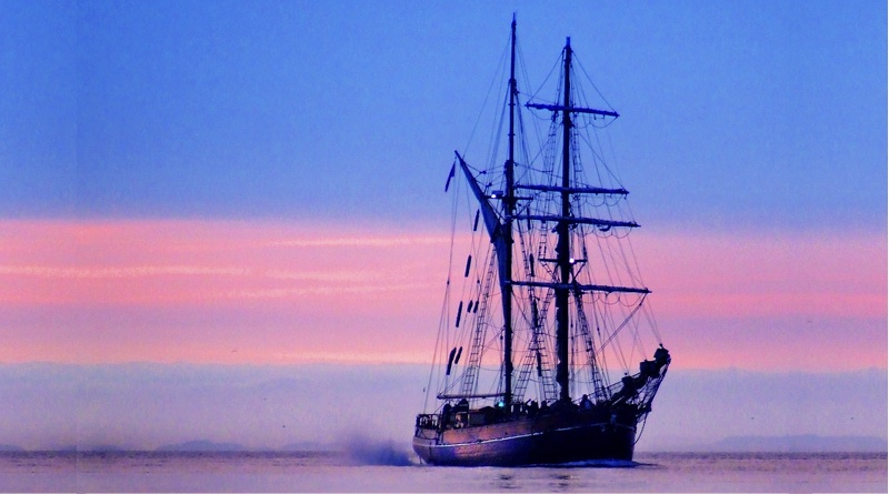 tall ship with electric motor sailing at beautiful sunset
