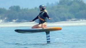 woman beginner kneeling o gyroscopic e-foiling surfboard