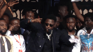 Medikal and the AMG Business crew on stage after receiving award