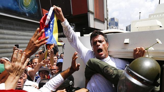Leopoldo López sostiene una bandera de Venezuela mientras es arrestado