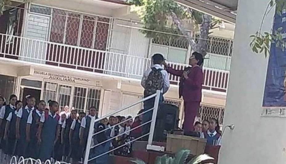 Directora corta cabello de alumno frente a toda la escuela