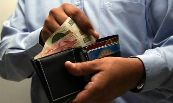 joven trabajador ve su cartera y sabe en tendrá mal sueldo y no contara con seguro social