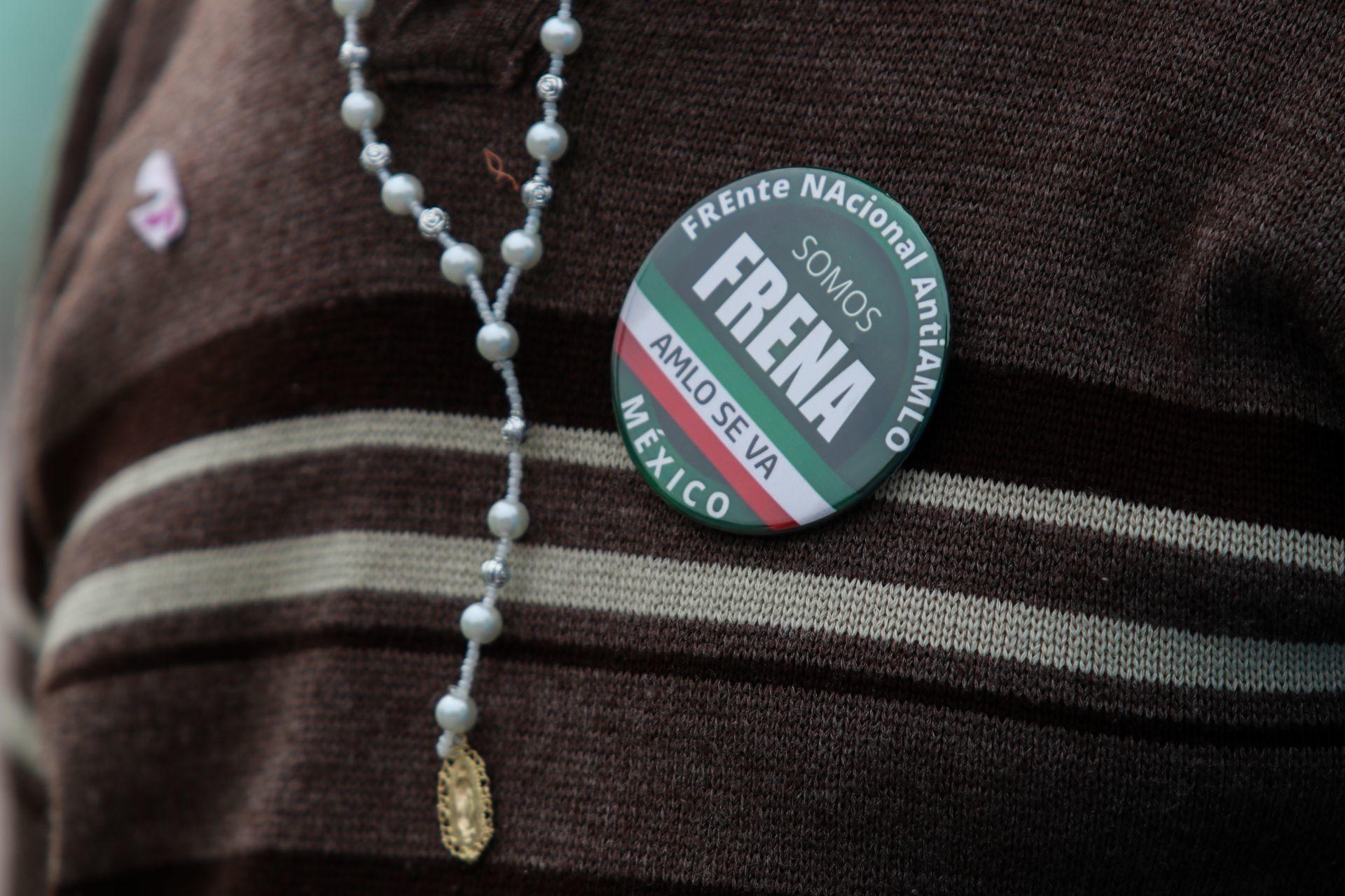 Integrante de FRENAAA en el Zócalo porta un rosario