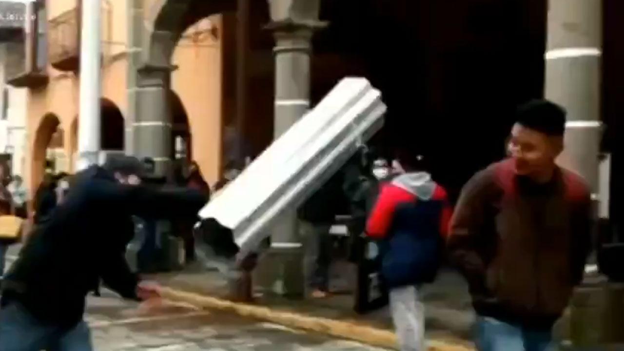 En Huauchinango, Puebla, un video muestra como un comerciante golpea con una lámina a un hombre por no traer cubrebocas