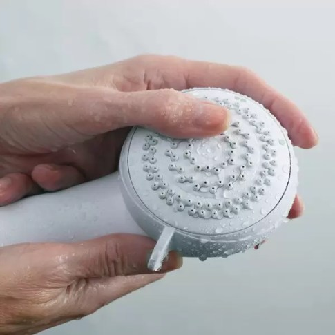Woman rubbing the nozzels of shower