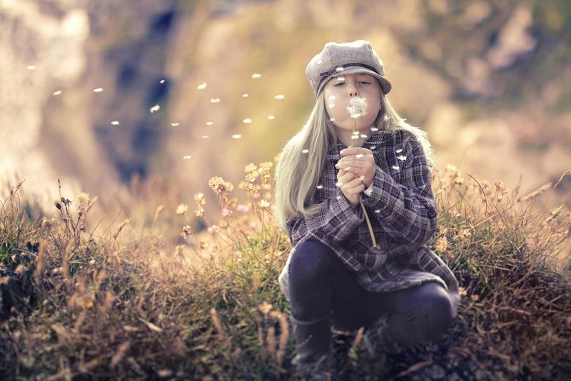 femme dans la forêt en train de souffler les graines d'un pissenlit