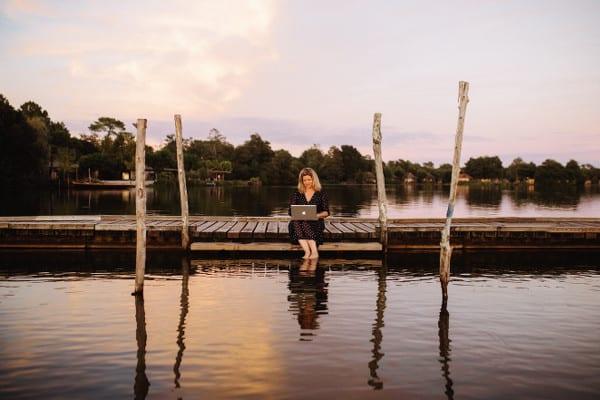 Claire Pimenta de Miranda en train d'écrire sur son ordinateur assise sur un ponton au bord du lac