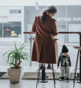Woman working at high cafe table while her toddler stands beneath it