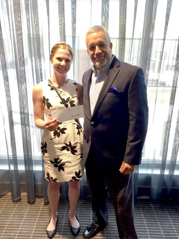 Whitney Tabash - handing the Travis County Center for Child Protection's Executive Director, Michael Torres, a check from the PLUS Foundation at the organization's annual Caring for Kids Banquet April 27th
