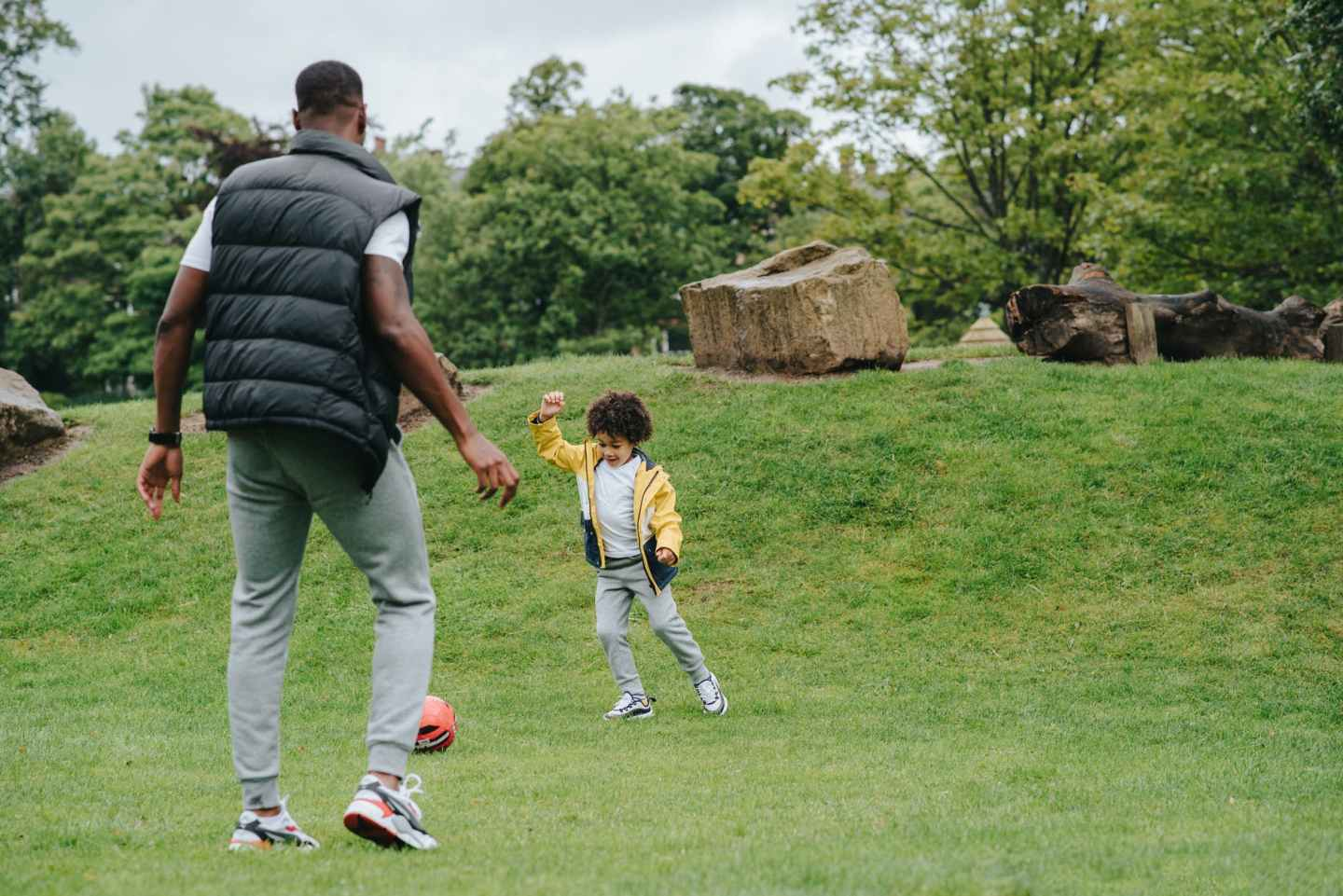 playful black boy playing football with father