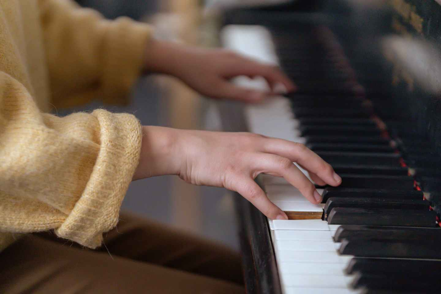 faceless woman playing piano in studio