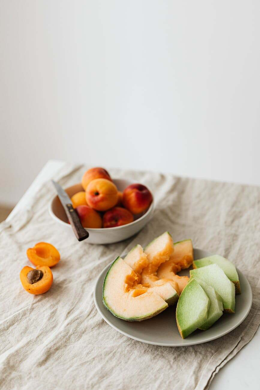 plate of fresh assorted melons served on table with bowl of ripe apricots