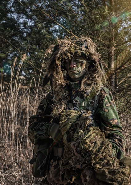 Camouflaged soldier during patrol in sunny day