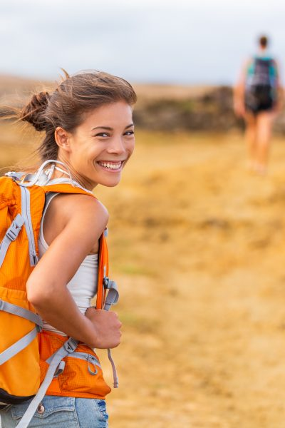 Happy young Asian hiker girl hiking with friend in mountain nature trail wearing orange backpack smiling looking back enjoying travel holiday in summer. Adventure wanderlust lifestyle. Healthy woman.