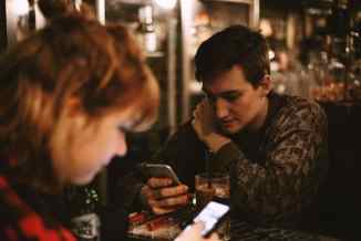Couple sitting at table on phones