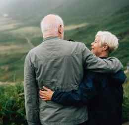 Two older people embracing on mountain