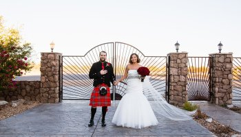 Bride and groom in front of the Supersition mountains at their wedding at the Supersition Manor by wedding photographers PMA Photography.