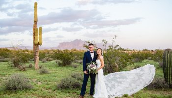 Bride and groom together in the desert with the Superstition Mountains by Arizona wedding photographer PMA Photography.