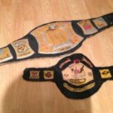 "Two early cardboard belts I made, the spinner (missing its logo) & my first belt the ""Champion of the Unevurce"" Belt!"