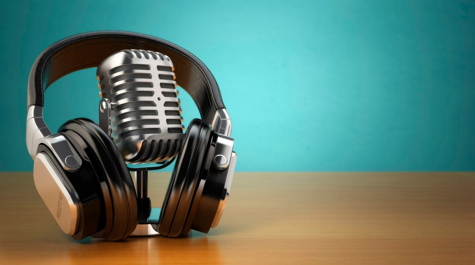 Vintage microphone and headphones on green background.