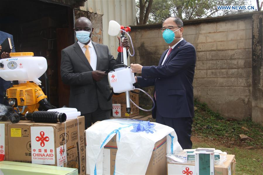 Chinese Ambassador to Uganda Zheng Zhuqiang (R) hands over donated equipment to Vincent Ssempijja, Uganda's minister of agriculture, during a donation ceremony in Kampala, capital of Uganda, on June 10, 2020. China on Wednesday donated an assortment of chemicals and equipment to Uganda in the fight against desert locusts in the east African country. (Xinhua/Zhang Gaiping)